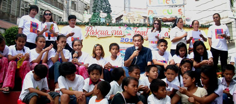 Hon. Mayor Celso L. Lobregat (seated with microphone) sings 'The Journey' with the children and some anti-human trafficking advocates.