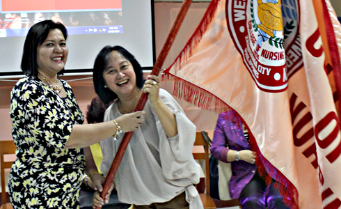 Outgoing dean Prof. Leila D. Benito (right) turns over the College of Nursing banner to the newly installed dean Dr. Nursia M. Barjose (right).