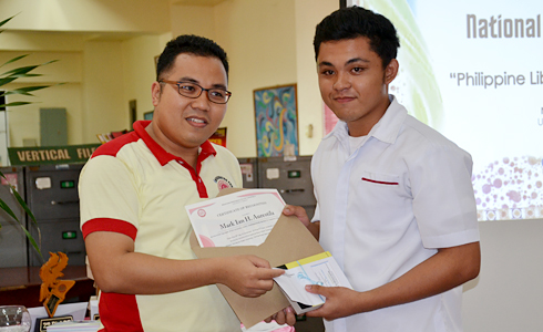 University Librarian, Mr. Benhur Asid, presents the award as best library user (student category) to Mark Ian Aurestila from CET.